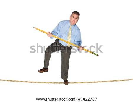 A businessman balancing on a tightrope using a giant pencil as a balancing pole.  Image is good for business risk and success inferences. - stock photo