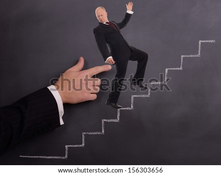 a businessman being pushed poked up stairs on a chalkboard background