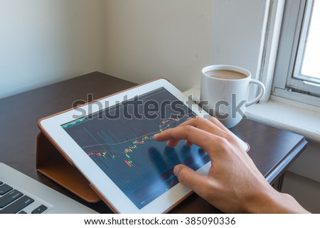 A businessman check stocks and market data on a touch screen device. Trading on stock market concept. - stock photo