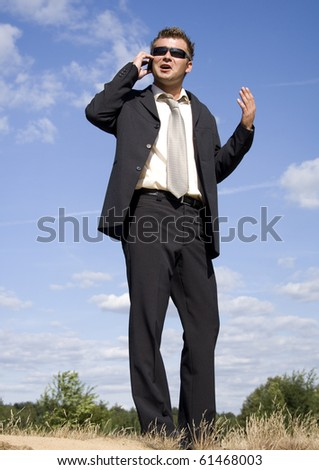 A businessman dressed in a smart suit standing on grass