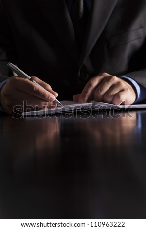 A businessman dressed in a suit sits at a desk and writes in a notebook. - stock photo