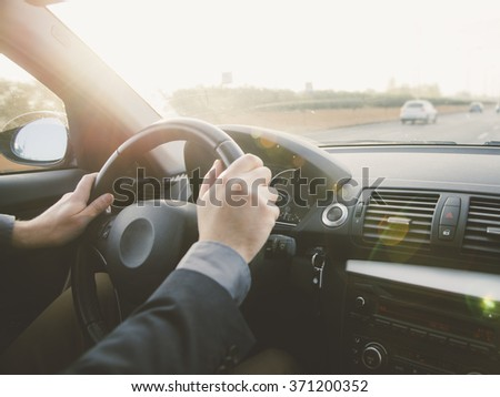 A businessman driving on a highway , vintage look and sun flare