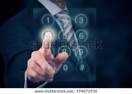 A businessman entering a password onto a glass screen keypad. - stock photo