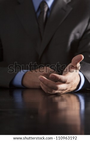 A businessman extends his hand out towards others. - stock photo