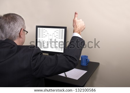 A businessman giving thumbs up looking at his March Madness bracket - stock photo