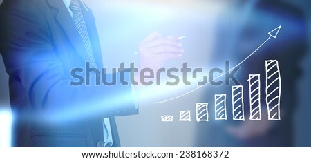 A businessman hand writing a business graph  - stock photo