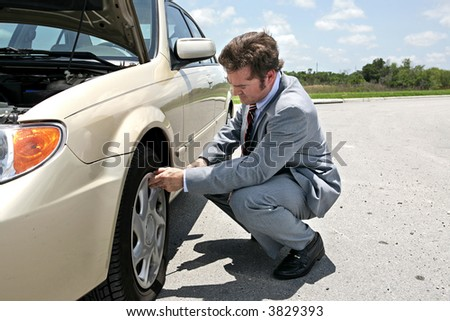 A businessman has a flat tire on the road.  He's getting ready to change it. - stock photo