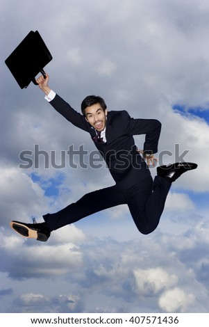A businessman holding a briefcase, leaping in the air - stock photo