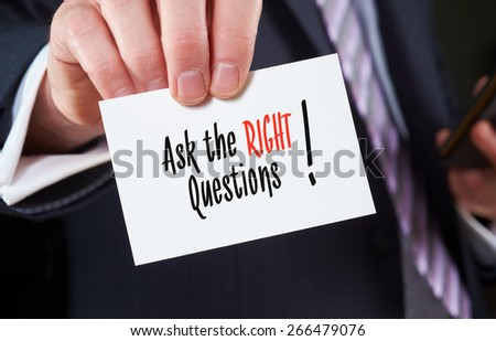 A businessman holding a business card with the words, Ask the Right Questions, written on it. - stock photo