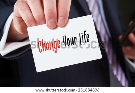 A businessman holding a business card with the words,  Change Your Life, written on it. - stock photo