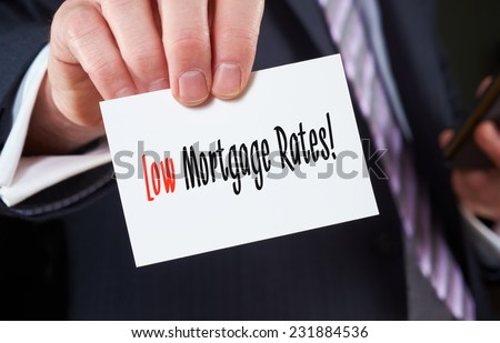 A businessman holding a business card with the words, Low Mortgage Rates, written on it. - stock photo