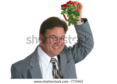 A businessman holding a sprig of mistletoe over his head.
