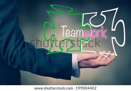 A Businessman holding a Teamwork puzzle concept. - stock photo