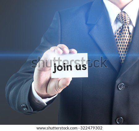 A Businessman holding a white sign with the message Join us. Can bring to the medium of your ad. - stock photo