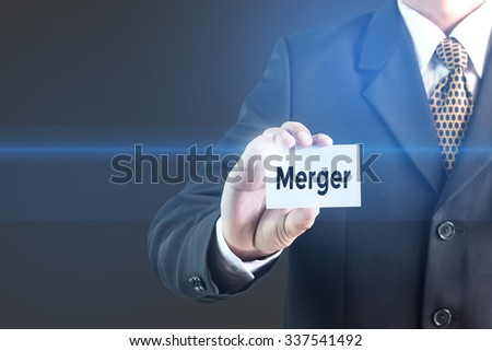 A Businessman holding a white sign with the message Merger. Can bring to the medium of your ad. - stock photo