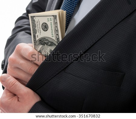 A businessman in a black suit putting money in his pocket isolated on white background