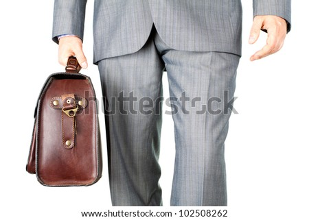 A businessman in a business suit carrying a briefcase (Isolated business background) - stock photo