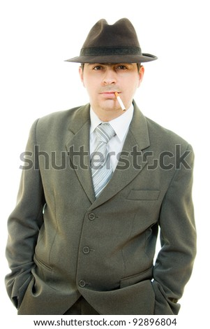 A businessman in a hat smokes on a white background. - stock photo