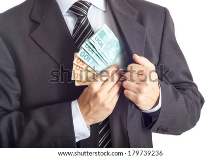 A businessman in a suit putting money in his pocket isolated on white background - stock photo