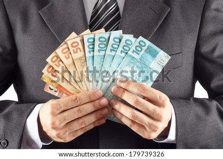 A businessman in a suit showing brazilian money - stock photo