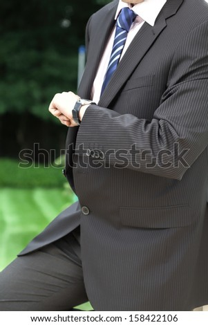 A businessman in a suit waitning and checking the time