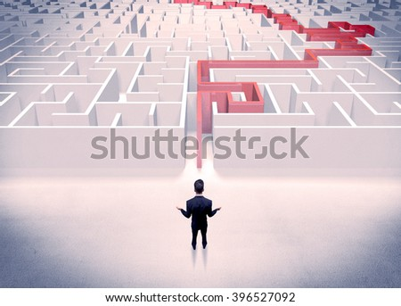 A businessman in suit giving thumbs up in front of labyrinth with red line showing the way out