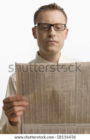 A businessman intently reads the newspaper.  Vertical shot.  Isolated on white. - stock photo