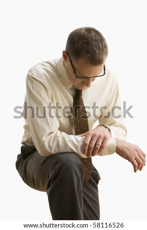 A businessman is leaning on his knee and looking down.  Vertical shot.  Isolated on white. - stock photo