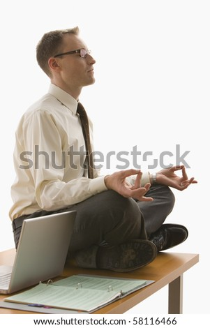 A businessman is meditating on his work desk next to his laptop.  Vertical shot.  Isolated on white. - stock photo