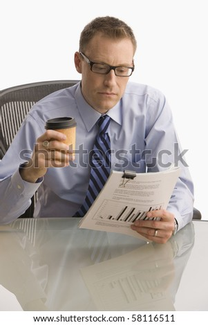 A businessman is seated at a desk and is looking at paperwork.  He is holding his coffee in one hand and reports in the other.  Vertical shot.  Isolated on white.