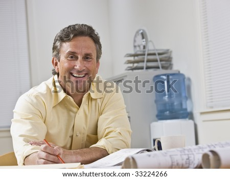 A businessman is seated at a desk in an office.  He is smiling at the camera.  Horizontally framed shot.