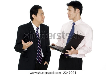 A businessman is shows his disappointment with a younger colleague holding a laptop computer - stock photo