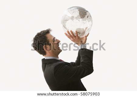 A businessman is smiling and wearing glasses while standing and holding a clear globe like he is shooting a basketball. Horizontal shot. Isolated on white. - stock photo