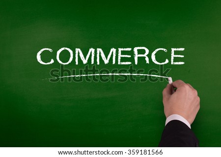 A businessman is writing COMMERCE concept on blackboard.