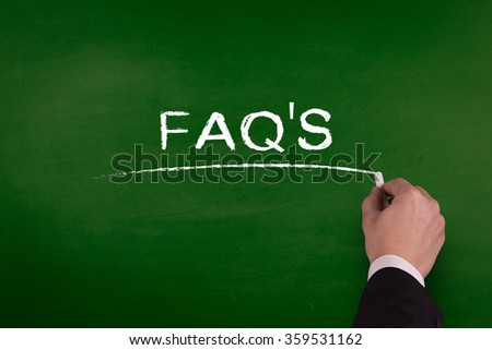 A businessman is writing FAQ'S concept on blackboard. - stock photo