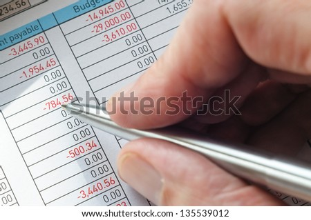 A businessman is writing on a financial form with a silver metallic pen