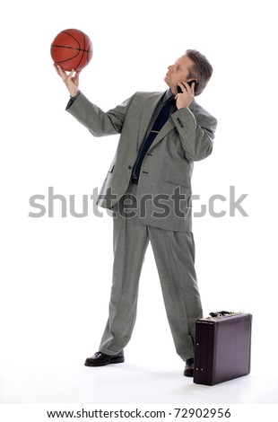 A businessman looking at a basketball - stock photo