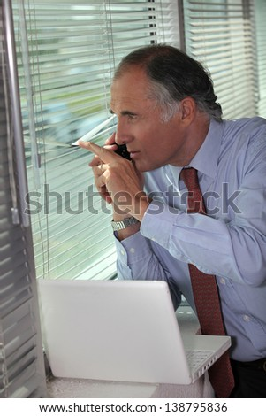 A businessman looking through the blinds. - stock photo
