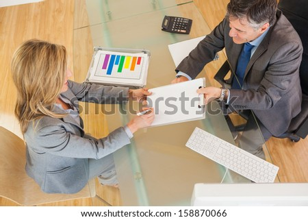 A businessman making a businesswoman signing a contract in an office above a desk - stock photo