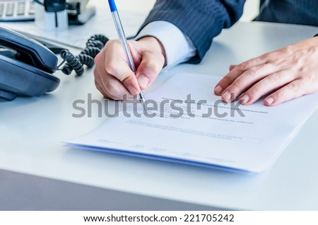 A businessman marks in a list and indicates some necessary documents to a customer for making a buy - stock photo