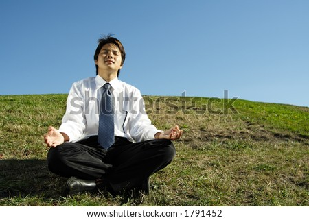 A businessman meditating in a park