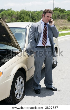 A businessman on the road with a flat tire.  He's calling his next appointment to say he will be late. - stock photo