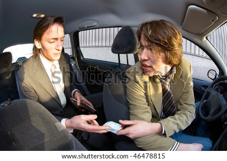 A businessman paying the fare to the taxi driver - stock photo
