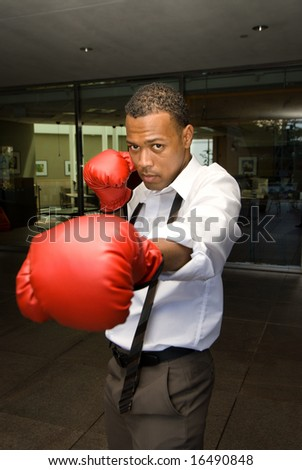 A businessman poses with his boxing gloves inferring that business is a dog eat dog world and very competitive.