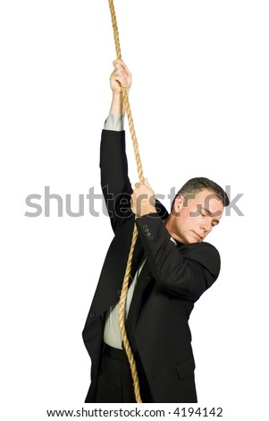A businessman precariously holding on to a rope looking down at what is below him. - stock photo