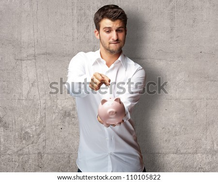 A Businessman Putting A Coin Into A Pink Piggy Bank, Indoor - stock photo