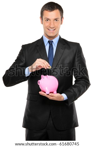A businessman putting a coin into a pink piggy bank isolated on white background - stock photo