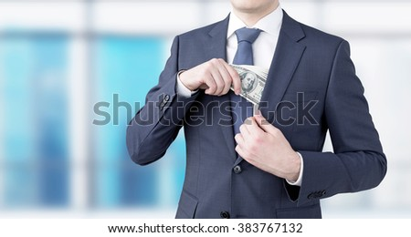 A businessman putting a one-hundred dollar banknote into the chest pocket. Blurred window at the background. Front view, no head. Concept of getting money. - stock photo