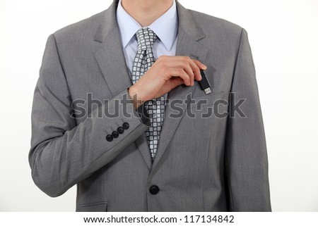A businessman putting his Usb key in his pocket. - stock photo