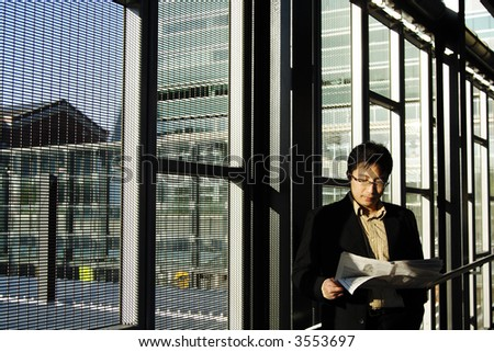 A businessman reading financial newspaper on a train station - stock photo